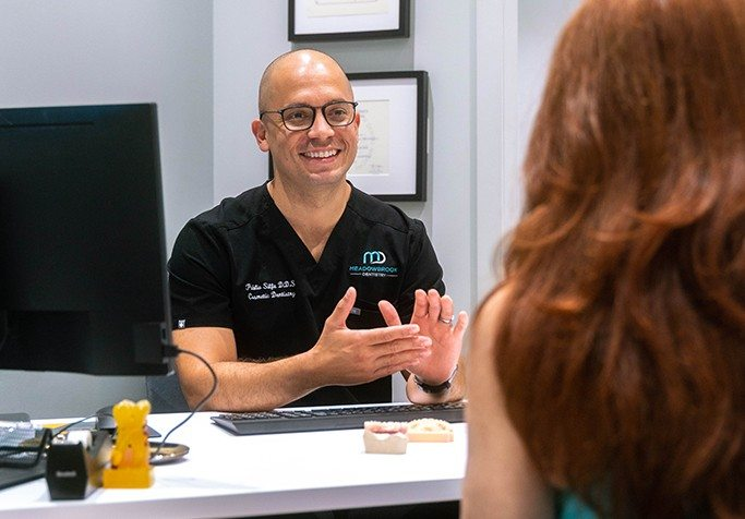 plainview dentist at desk with computer smiling