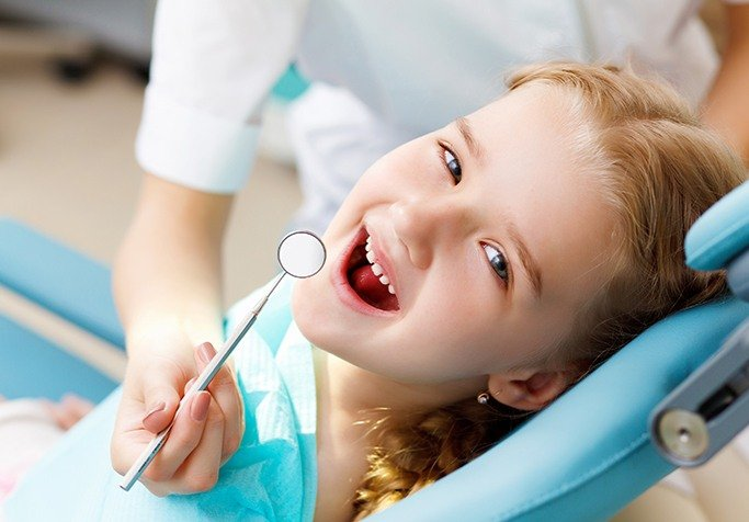 young girl in exam chair smiling at camera