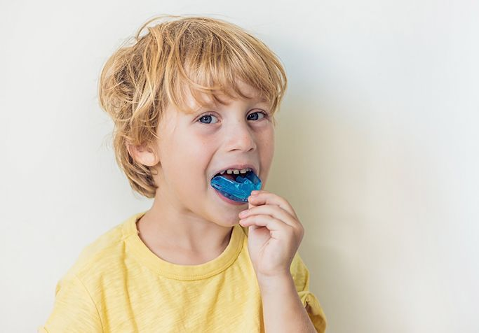 boy putting in sports mouthguard