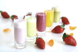 row of smoothies next to strawberries and orange slices