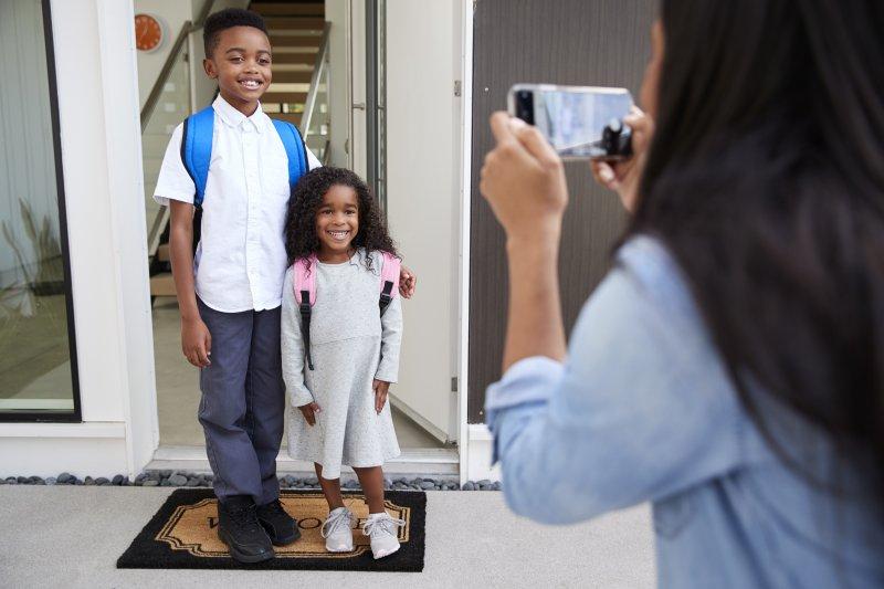 Mother taking photo of children before school