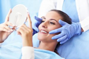woman admiring her smile after getting cosmetic dentistry work