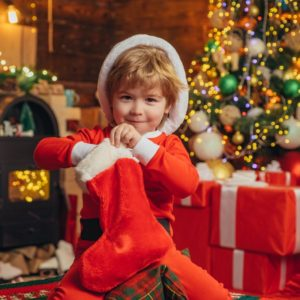 little kid pulling stocking stuffers out of their red stocking