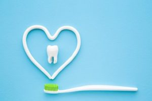 A heart shape drawn with toothpaste above a toothbrush with a tooth in the center against a blue background